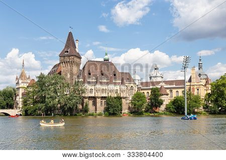 Budapest Vajdahunyad Castle Viewed From Its Lakeside And People With Blurred Faces In Boats