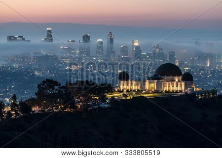 Los Angeles, California, USA - November 10, 2019:  Foggy morning dawn view of Griffith Park Observatory. with downtown Los Angeles skyline in background.