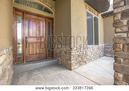 Home Porch And Brown Wood Front Door With Sidelights And Arched Transom Window