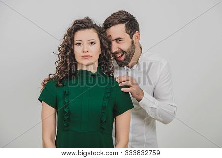 Man Has A Grin As If He Thought Up To Do Something Funky And Insidious To His Girlfriend, That Stand
