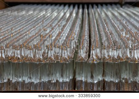 Glassworks. Glass Industry. Many Glass Bottles On A Factory Conveyor In A Row