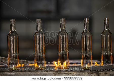 Glassworks. Glass Industry. Glass Bottle On Conveyor On Fire
