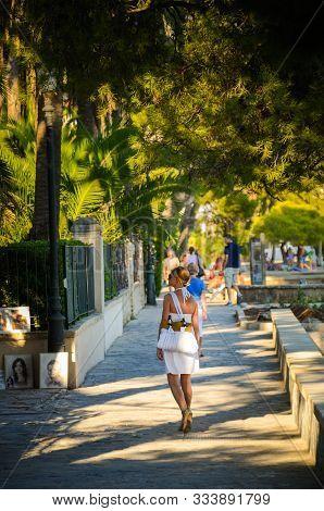 Pollenca Port, Majorca, Spain - 08.09.2011 : Woman In White Dress Walks Allong Port Street. Many Art