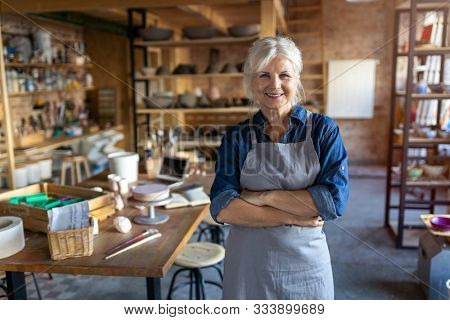 Portrait of senior female pottery artist in her art studio