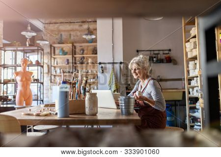Mature woman pottery artist using laptop in art studio