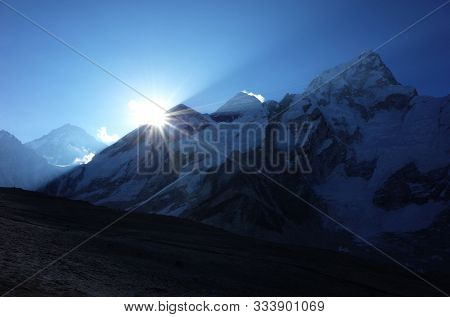 Everest trek, On the way to Kala Patthar - first sun shining from behind mountains, (Everest is in the middle with shiny blowing away snow). Sagarmatha national park, Solukhumbu, Nepal