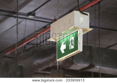 Fire Exit Sign Hanging On Top Of The Building. Fire Exit Sign Indicating Safe Route.