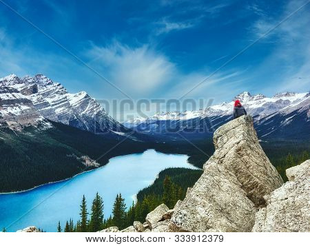 Peyto Lake, Banff National Park In Canada With The Canadian Rockies In The Distance, And A Woman Sat