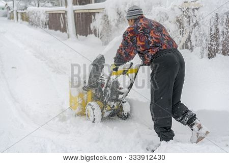 Man Operating Snow Blower To Remove Snow On Driveway. Man Using A Snowblower. A Man Cleans Snow From