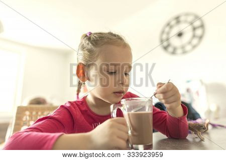 Little Girl Drinks Tea At Home In The Kitchen Behind The Table