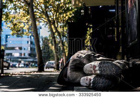 Homeless Man, Poor Homeless Man Or Refugee Sleeping On The Concrete Sidewalk Floor Ground On The Urb