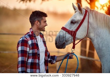 Happy man bonding with his horse, human equine relationship
