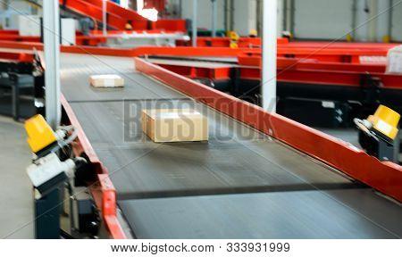 Empty Conveyor Sorting Belt At Distribution Warehouse. Distribution Hub For Sorting Packages And Par