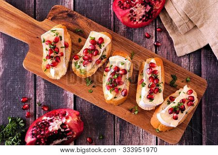 Holiday Crostini Appetizers With Brie Cheese, Pomegranates And Parsley. Above View On A Serving Boar