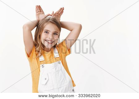 Cute Lovely Charming Little Girl, Blond Child In T-shirt, Overalls, Show Bunny Ears Mimicking Rabit,