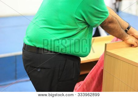 Side View Of A Large Tummy Of A Morbid Obese Person Without Face In Green T-shirt And Black Trousers