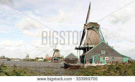 Amsterdam, Netherlands-october, 12, 2017: Windblown Reeds And Windmills At Zaanse Schans Near Amster