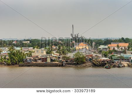 Long Tau River, Vietnam - March 12, 2019: Riverside Phuoc Khanh Village With Multiple Houses. Closeu