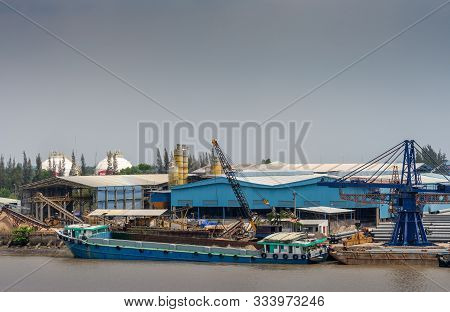 Long Tau River, Vietnam - March 12, 2019: River Cargo Boat Docked On Quay In Front Of Blue Atelier,