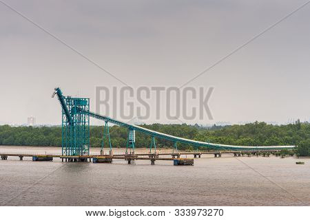 Long Tau River, Vietnam - March 12, 2019: Azure Blue Dock And Pipeline Installation Built On Brown W