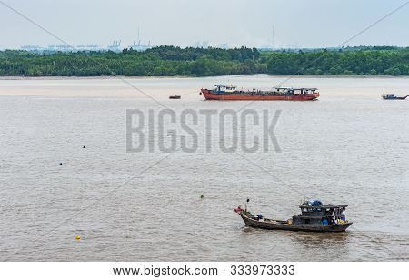 Long Tau River, Vietnam - March 12, 2019: Wide Brown River With 2 Smaller Vessels. Green Belt On Sho