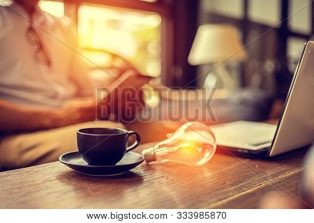 Light Bulb On The Table Near Cup Of Coffee And Laptop. Idea, Business Concept