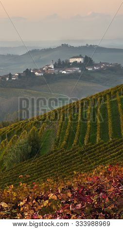 Beautiful Italian Landscape -evening Over Piemonte Hills With Vineyards With Little Village On The T