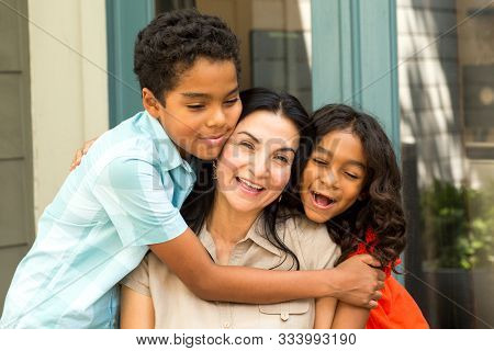 Happy Hispanic Mother Laughing And Talking With Her Children.