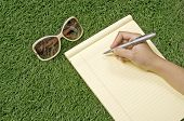 People writing on the paper over green grass. You can write your message on the paper poster