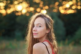 Beautiful Teen Girl Is Smiling And  Enjoying Nature In The Park At Summer Sunset