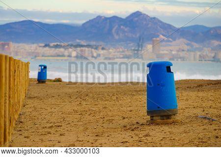 Coastal Landscape, Empty Beach Shore With Trashcan, Alicante City In The Distance. Spain, Costa Blan