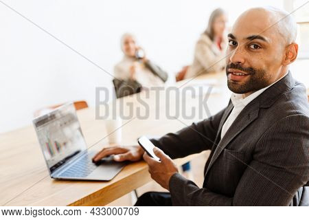 Unshaven man working with laptop and cellphone at office