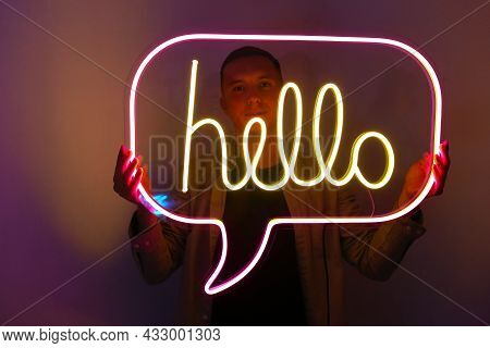 Handsome Young Man Holding Pink And Yellow Neon Sign Hello.   Trendy Style. Neon Sign. Custom Neon.
