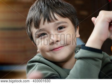 Close Up Face Of Cute Little Child Boy Looking At Camera With Smiling Face, Candid Shot Mixed Race K