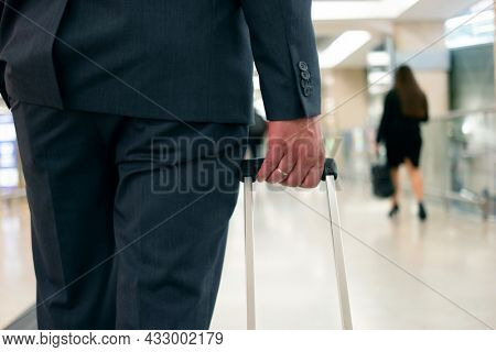 Detail of a businessman pulling a trolley in an airport
