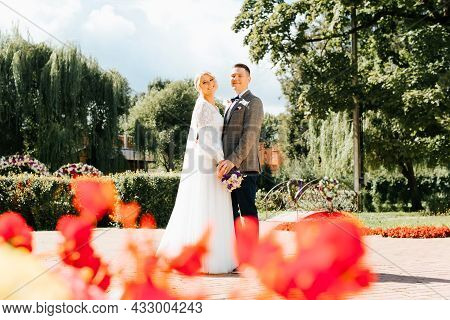 Happy Young Married Couple Holding Hands, Groom In Suit And Beautiful Bride In White Dress With Bouq