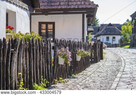 Old Rural House And Yard With Flowers In Ethnographic Village Holloko In Hungary And A Unesco World
