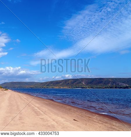 The Sandy Shore Of The Big Volga River Against The Background Of Blue Cloudy Sky. On The Opposite Ba
