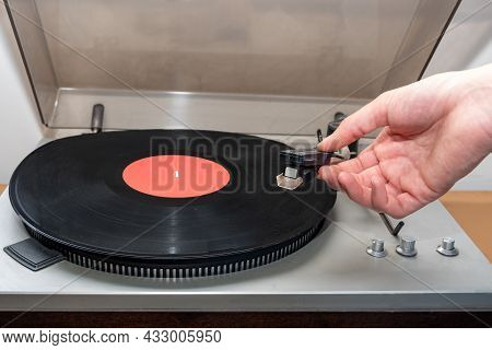 Hand Turning On Stereo Turntable Analog Retro Vintage. An Old-fashioned Plastic Turntable Playing A