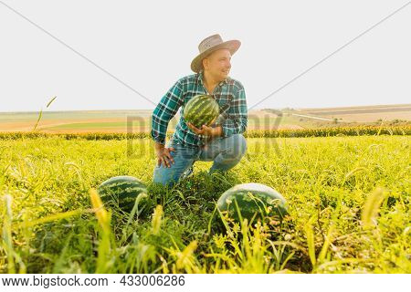 Farmer Smiles And Looks At The Camera, Holding A Big Watermelon In His Hand. Male Farmer With Hat On