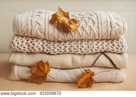Beautiful Soft Warm Wool Sweaters Are Stacked In A Pile, And Next To Them Are Dry Red Maple Leaves,
