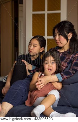 Asian Family Of Mom And Two Daughters Watching Video On Couch At Home, Relaxing Moments Together At