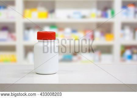 Blank White Medicine Bottle On Counter With Blur Shelves Of Drug In The Pharmacy Drugstore Backgroun