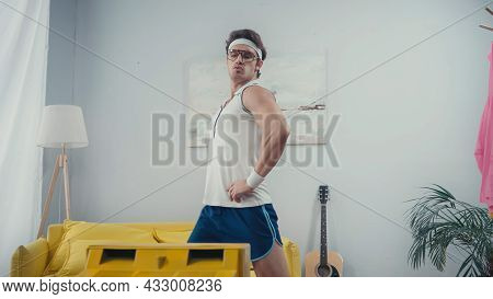 Funny Sportsman With Hands On Hips Doing Lunges In Front Of Retro Tv At Home