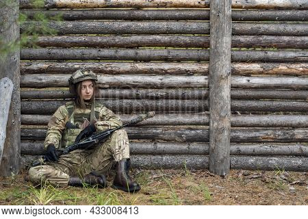 Girl In Military Uniform Holds An Automatic Rifle In Her Hands. Woman Soldier In Bulletproof Vest An