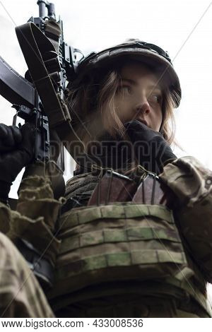 Portrait Of A Young Girl In A Military Camouflage Uniform With An Automatic Rifle In Her Hands Again