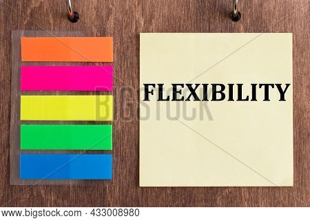 Yellow Paper With Text Flexibility On Wooden Background