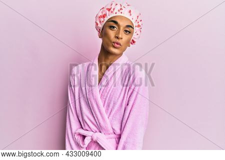 Hispanic man wearing make up wearing shower towel cap and bathrobe looking at the camera blowing a kiss on air being lovely and sexy. love expression.