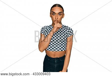 Hispanic transgender man wearing make up and long hair wearing modern clothes asking to be quiet with finger on lips. silence and secret concept.