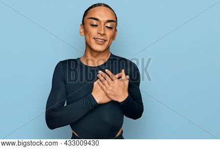 Hispanic transgender man wearing make up and long hair wearing casual clothes smiling with hands on chest with closed eyes and grateful gesture on face. health concept.